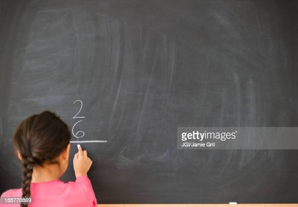 Mixed race girl doing math on blackboard