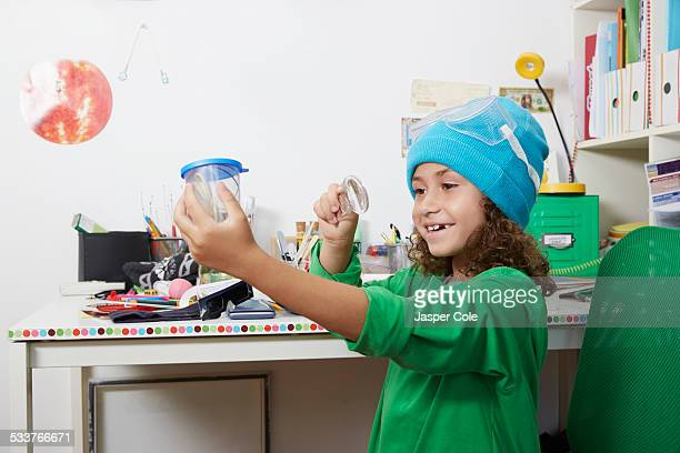 Mixed race girl doing science experiments at desk