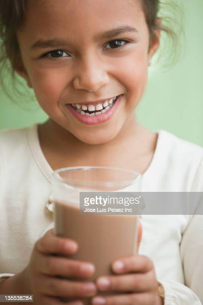 Mixed race girl drinking chocolate milk