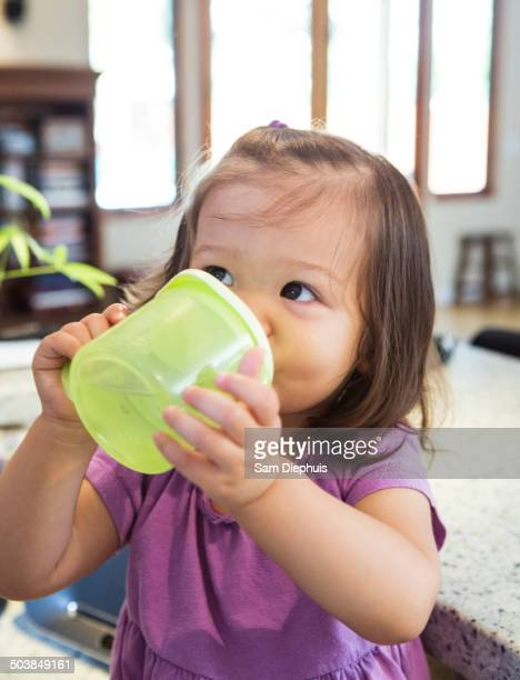 Mixed race girl drinking from sippy cup in kitchen