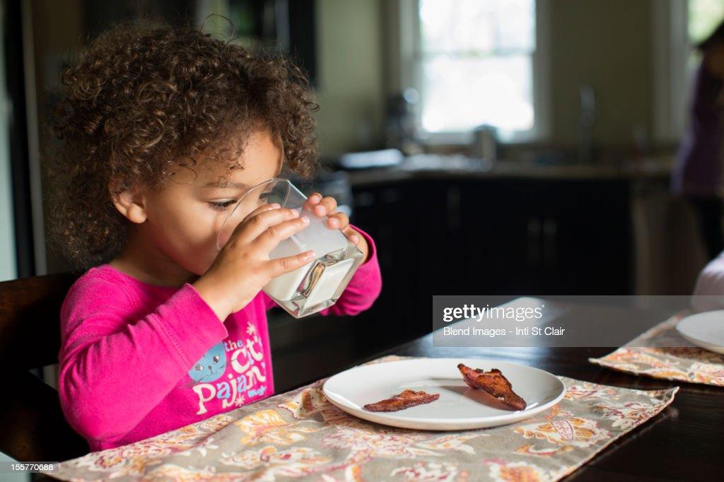 Mixed race girl drinking milk : Stock Photo