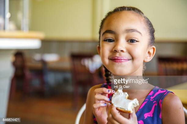 Mixed race girl eating bagel in cafe