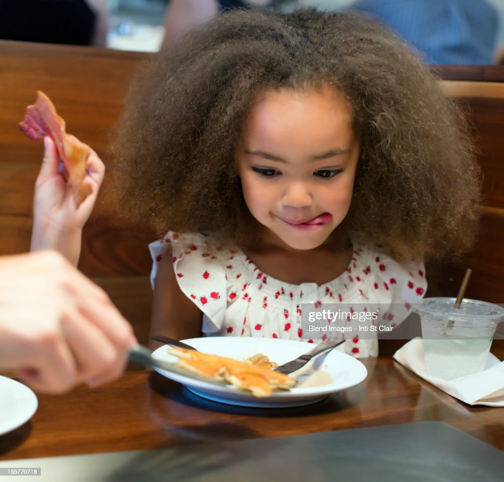 Mixed race girl eating breakfast in restaurant : Stock Photo