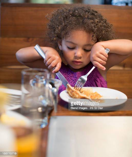 Mixed race girl eating breakfast in restaurant