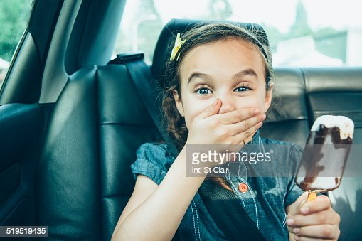 Mixed race girl eating ice cream bar in car back seat