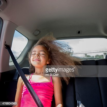 Mixed race girl enjoying wind in hair in back seat of car