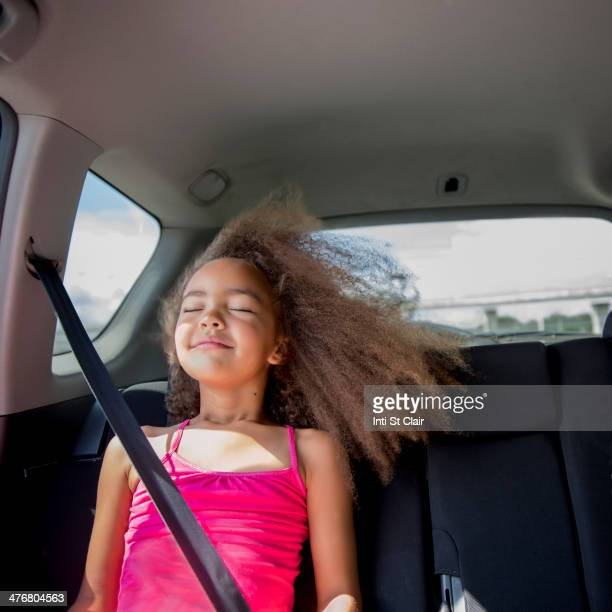 Mixed race girl enjoying wind in hair in back seat of car