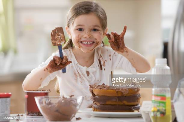 Mixed race girl frosting cake and making a mess