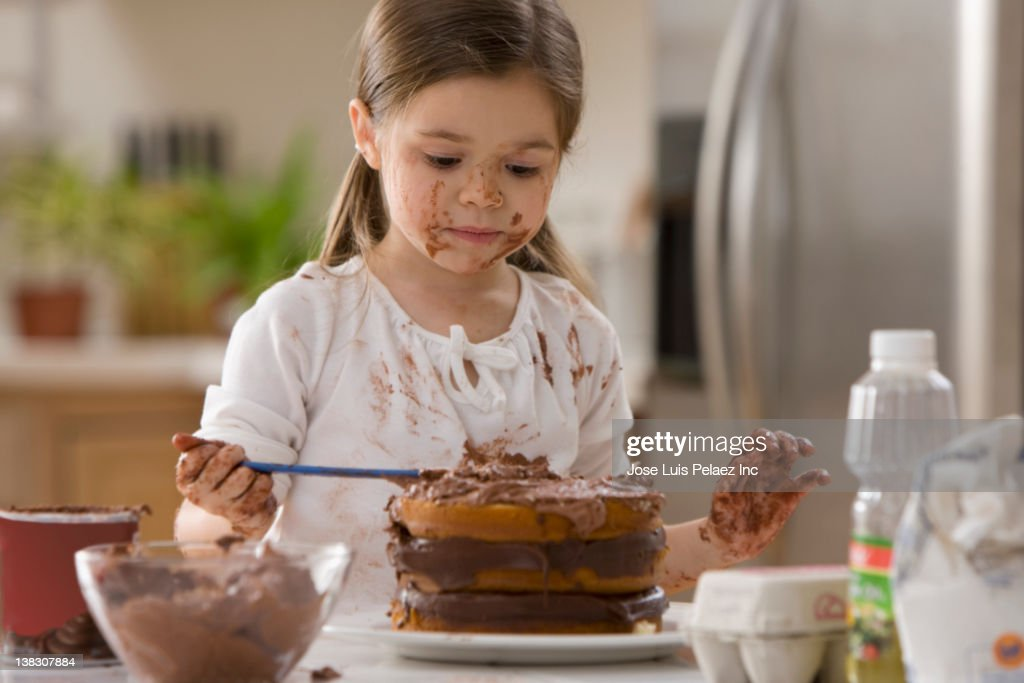 Mixed race girl frosting cake : Stock Photo