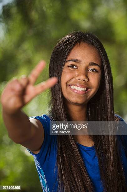 Mixed race girl giving peace sign