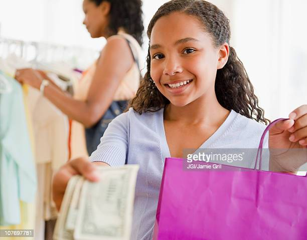 Mixed race girl handing over money in clothing store