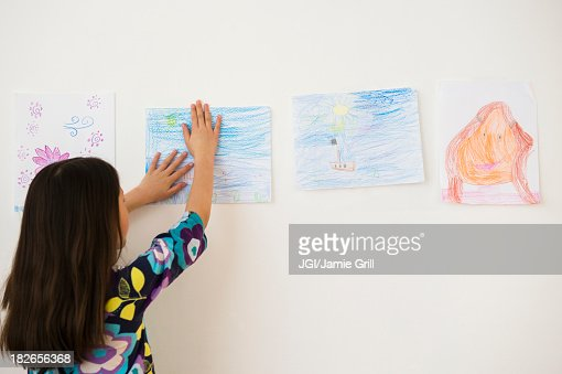 Mixed race girl hanging drawings on wall