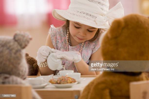 Mixed race girl having tea party with stuffed animals