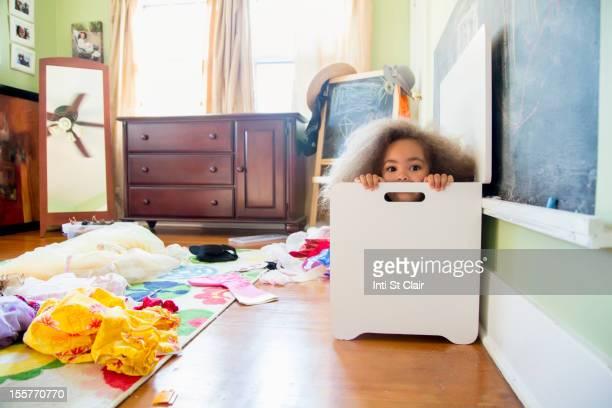 Mixed race girl hiding in hamper