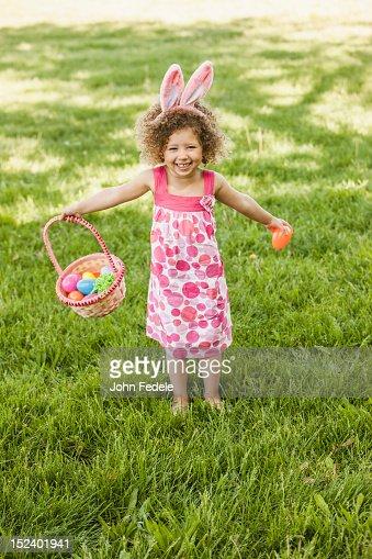 Mixed race girl holding basket of Easter eggs