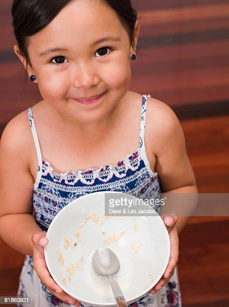 Mixed Race girl holding cereal bowl