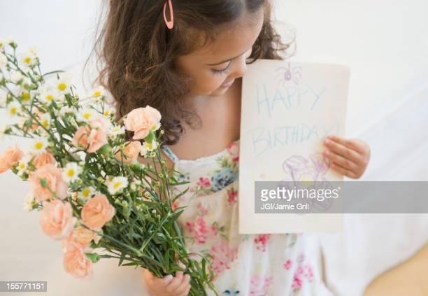 Mixed race girl holding flowers and birthday card