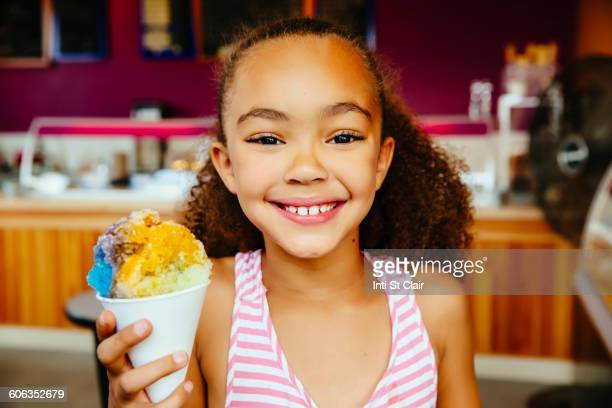 Mixed race girl holding snow cone
