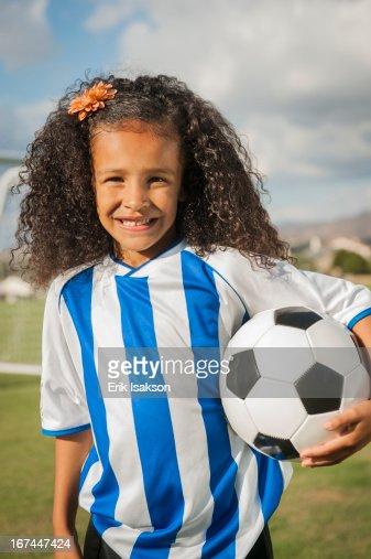 Mixed race girl holding soccer ball : Stock Photo