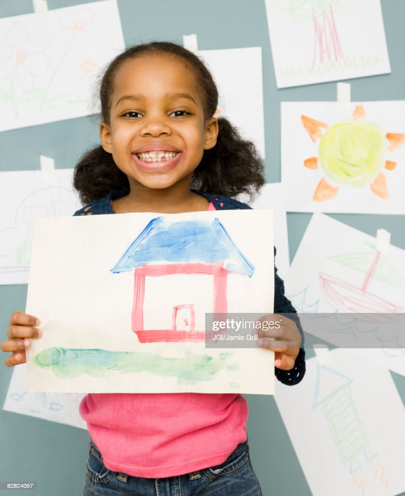 Mixed race girl holding water color painting of a house : Stock Photo