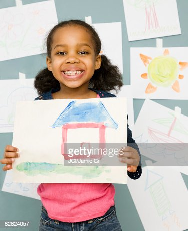 Mixed race girl holding water color painting of a house : Stock-Foto