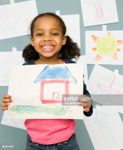 Mixed race girl holding water color painting of a house