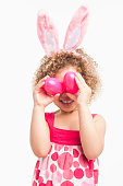Mixed race girl in bunny ears and holding Easter eggs