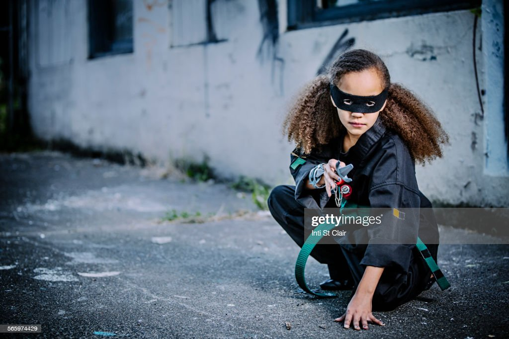 Mixed race girl in martial arts uniform and mask : Stock Photo