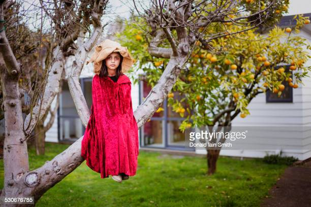 Mixed race girl in witch costume sitting in tree
