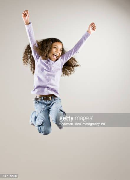 Mixed Race girl jumping in air
