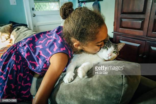 Mixed race girl kissing pet cat on sofa
