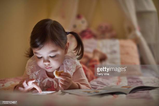 Mixed Race girl laying on bed eating snack and using cell phone