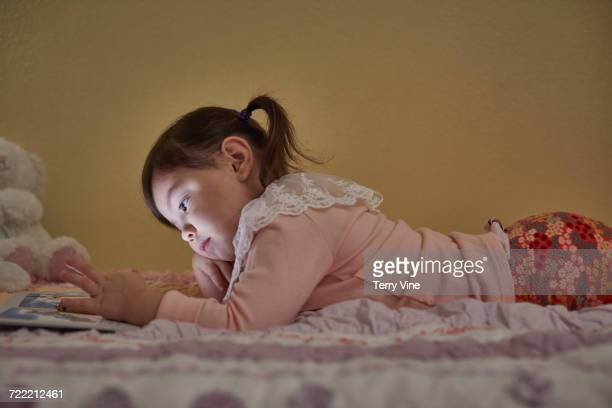 Mixed Race girl laying on bed using cell phone