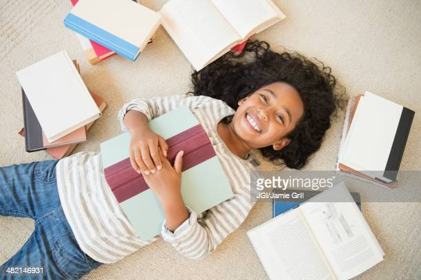 Mixed race girl laying on floor with books