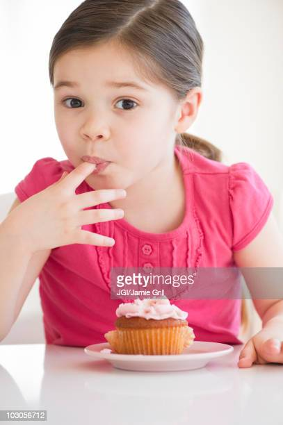 Mixed race girl licking frosting from finger