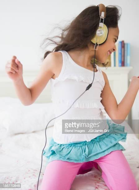 Mixed race girl listening to music on headphones