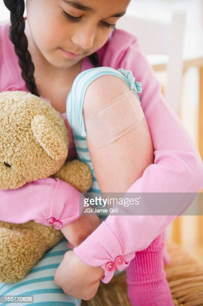 Mixed race girl looking at bandage on knee