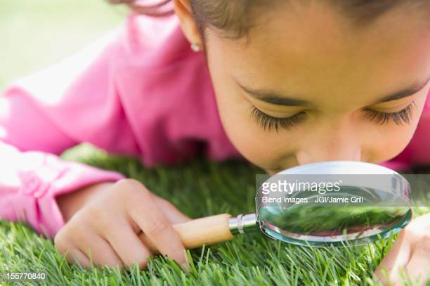 Mixed race girl looking at grass with magnifying glass