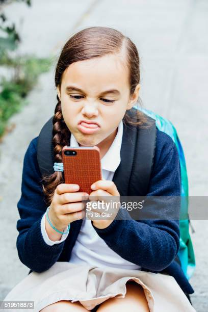 Mixed race girl making a face at cell phone