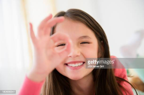 Mixed race girl making O.K. sign with fingers