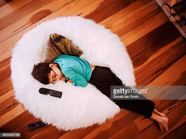 Mixed race girl napping in beanbag chair