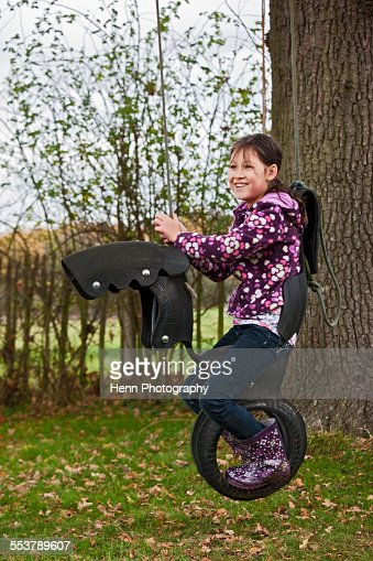 mixed race girl on horse swing that is made out of old tyres