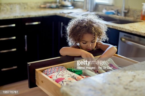Mixed race girl opening kitchen drawer : Stock Photo