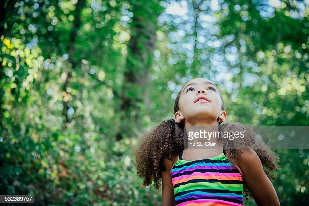 Mixed race girl outside looking up at trees