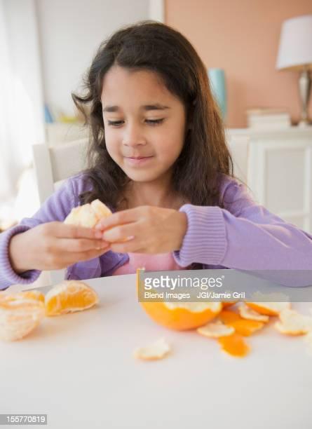 Mixed race girl peeling an orange