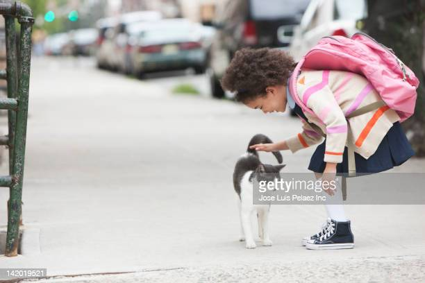 Mixed race girl petting cat on sidewalk