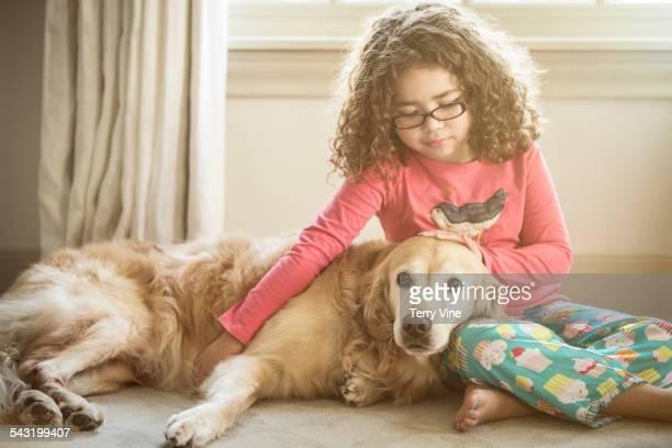 Mixed race girl petting dog on floor