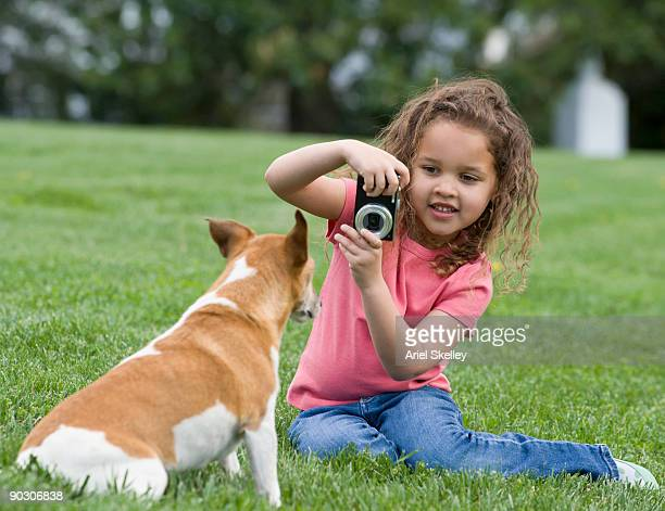 Mixed race girl photographing dog