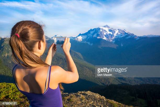 Mixed race girl photographing mountains, North Cascade Mountains, Washington, United States