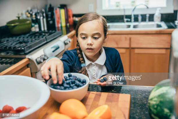Mixed race girl picking blueberries from bowl in kitchen